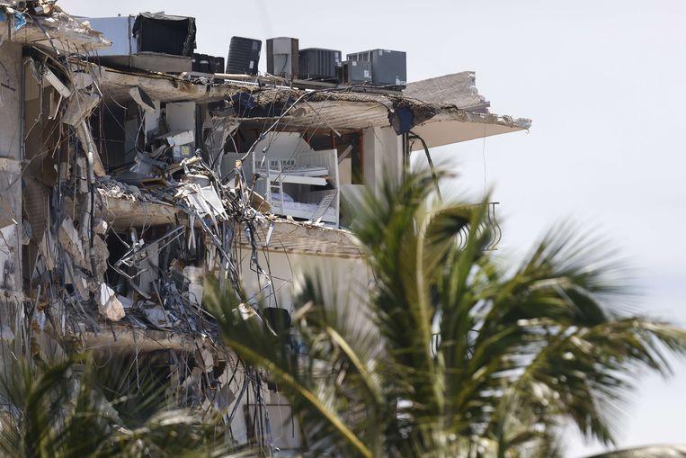 Een deel van het appartementencomplex staat nog overeind, maar is gevaarlijk instabiel.  Beeld AFP