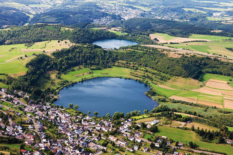 Op de voorgrond: het Weinfelder Maar, een cirkelvormig water in de Eifel dat ooit ontstond na een vulkanische eruptie.   Beeld Getty Images/Westend61