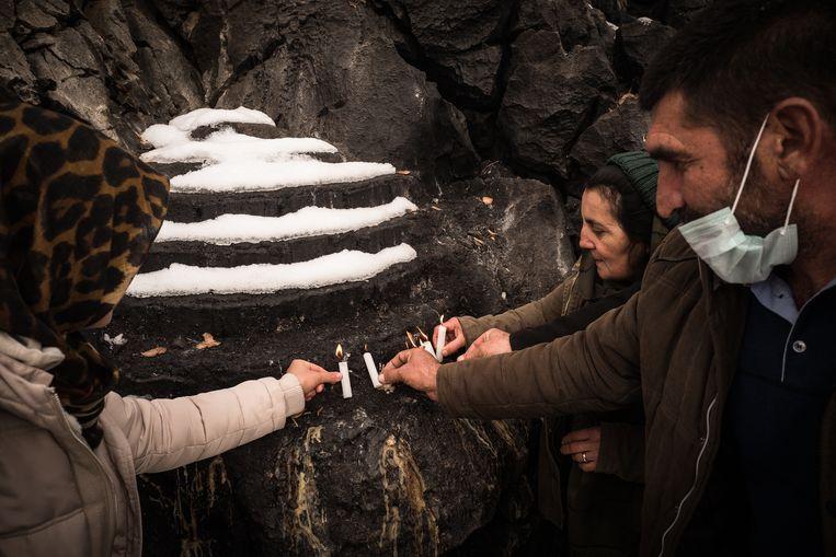 Koerdische alevieten branden kaarsjes bij de heilige rotsen. Beeld Nicola Zolin