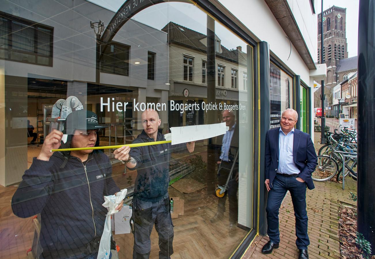 Tijn Verhoeven kijkt toe hoe de etalage aan de Kerkstraat wordt bestickerd. Bogaerts Optiek verhuist in mei naar de voormalige winkel van Miss Etam.