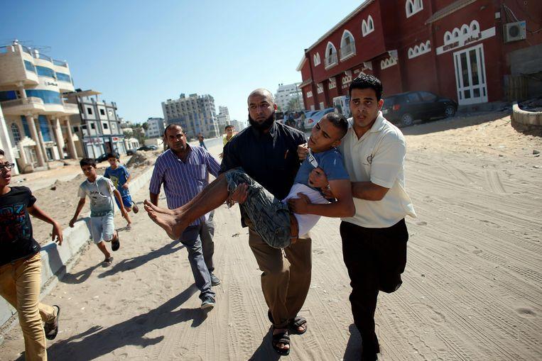 Een gewonde jongen wordt weggedragen in Gaza. Beeld AFP
