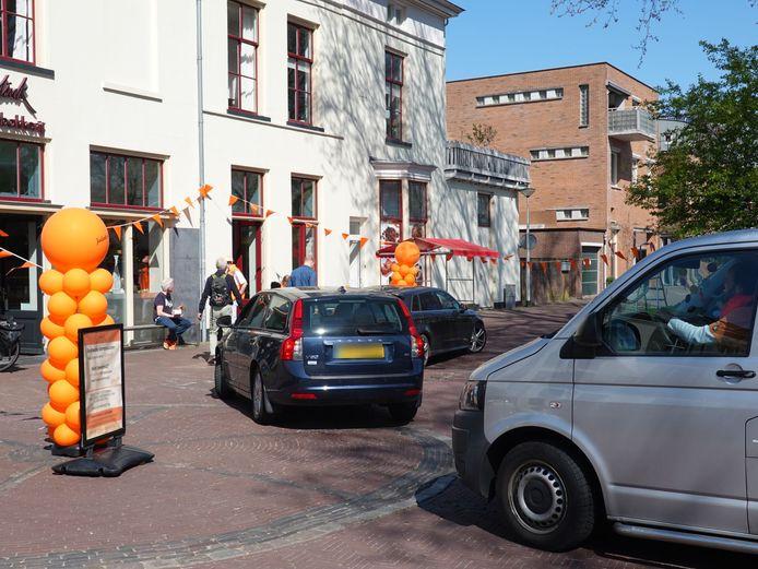 Automobilisten verzamelen zich voor Banketbakkerij Jolink in Zutphen voor een oranje tompouce.