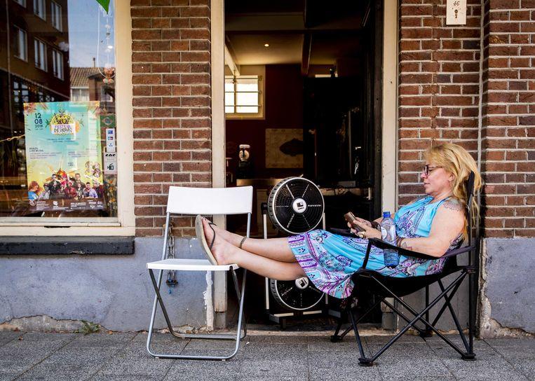 Een vrouw zoekt verkoeling voor haar winkel. Beeld ANP