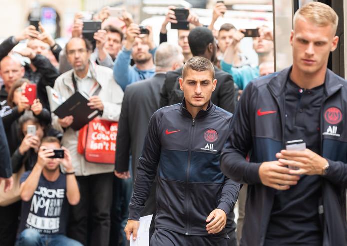 Bakker (r) arriveert bij het stadion voor Dinamo Dresden - Paris Saint-Germain. Links: ploeggenoot Marco Verratti.
