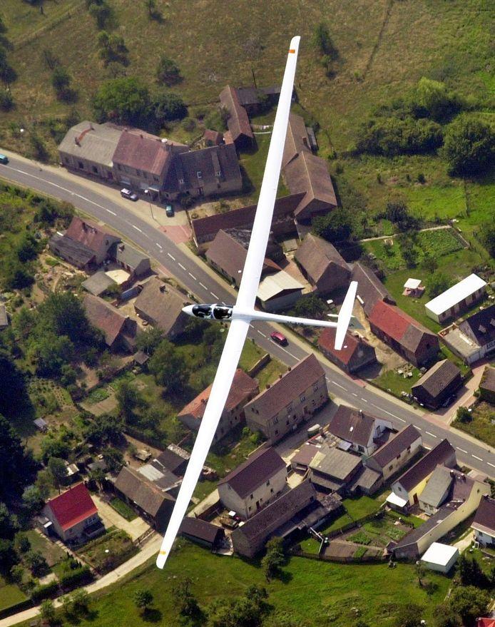 Een zweefvliegtuig boven de plaats Luesse in Duitsland