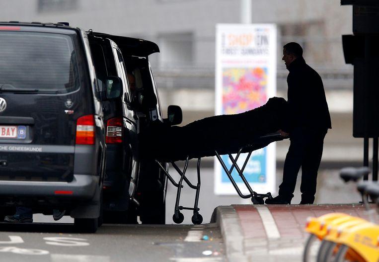 Het lichaam van een slachtoffer wordt weggedragen uit het metrostation Maalbeek, een dag na de aanslagen. Beeld EPA