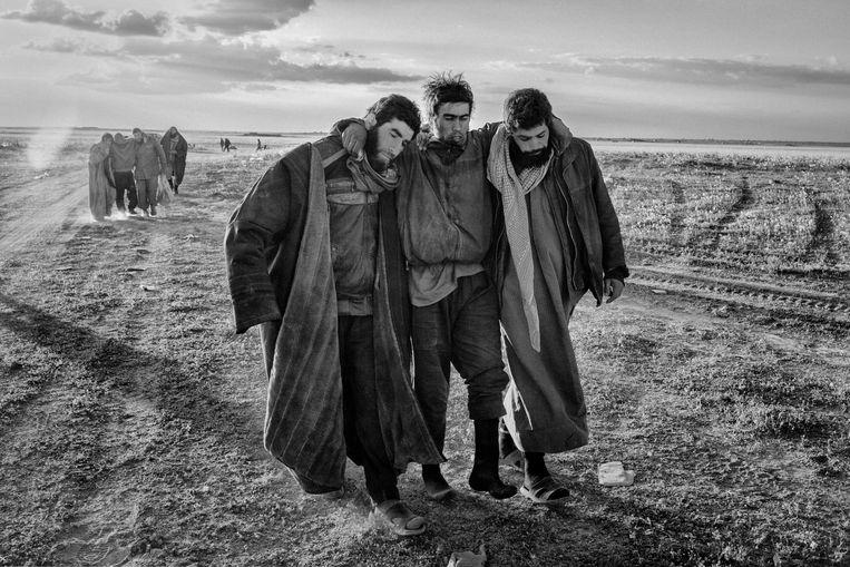 IS strijders ondersteunen hun gewonden en verlaten Baghuz, in de stad is geen eten of medische zorg meer aanwezig, zij worden gecontroleerd op explosieven door de SDF coalitie en gearresteerd. Beeld Eddy van Wessel