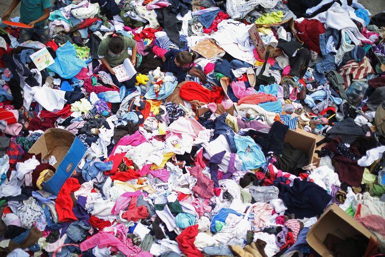 Migranten sorteren gedoneerde kleding in Hongarije. Beeld getty