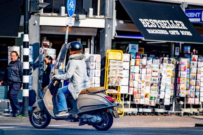 Niet alleen de snelle scooters met gele, maar ook de snorscooters met blauwe kentekenplaten moeten vanaf vandaag de rijbaan op in Amsterdam. Ook is de helmplicht ingevoerd.