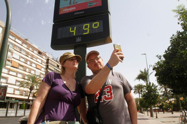 Toeristen nemen een selfie naast een thermometer in Cordoba, Spanje, waar het kwik tegen de 50 graden aanschurkt. Beeld EPA