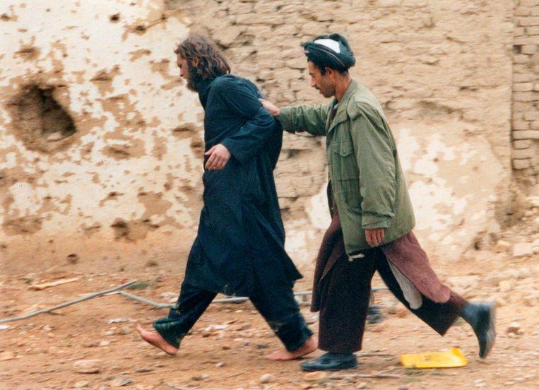 John Walker Lindh (links) in 2001, na zijn arrestatie in Mazar-i-Sharif, Afghanistan.   Beeld Foto Reuters