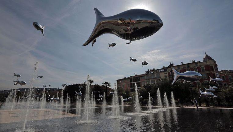 Ballonnen in de vorm van een vis zweven boven een fontein in Nice. Beeld REUTERS