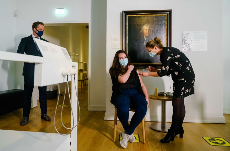 Huisarts Sylvia van den Berg van GGZ Rivierduinen dient onder het toeziend oog van demissionair minister Hugo de Jonge in Rijksmuseum Boerhaave een van de eerste prikken met het Janssen-vaccin toe bij een medewerker van de GGZ.  Beeld ANP