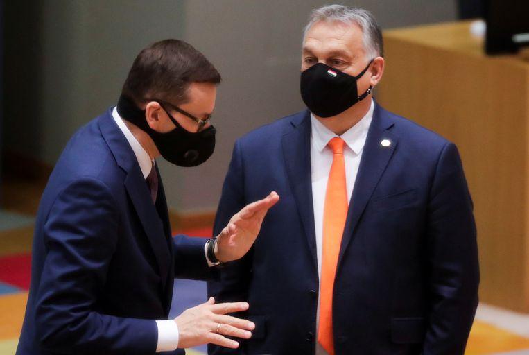 De Poolse premier Mateusz Morawiecki en zijn Hongaarse ambtgenoot Viktor Orbán donderdag tijdens de EU-top in Brussel. Beeld Reuters