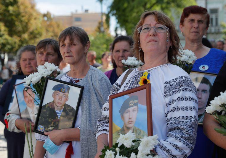 Oekraïense vrouwen met portretten van geliefden die in de strijd gesneuveld zijn, augustus 2020.   Beeld Hollandse Hoogte / EPA