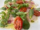 Carpaccio van zeebaars met tomaatjes en rucola