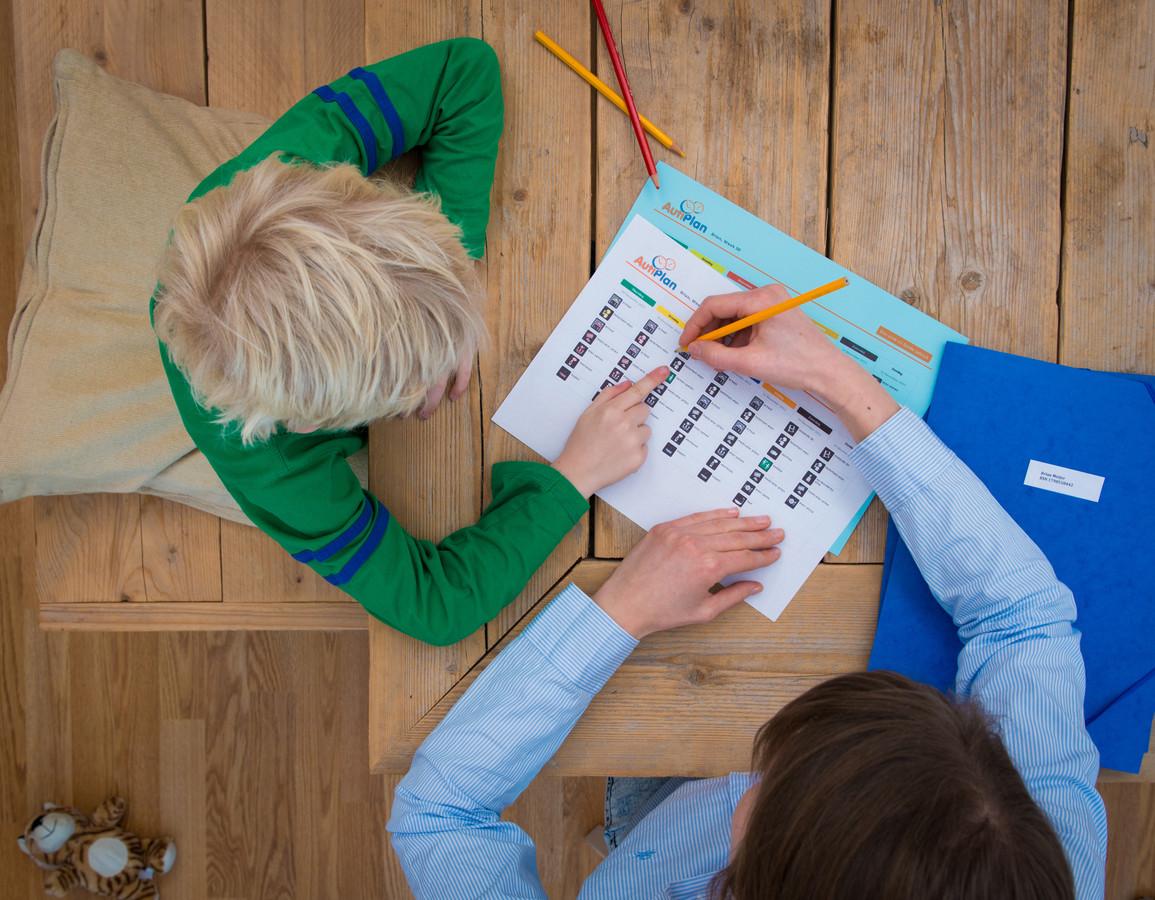 Een jeugdhulpverlener helpt een jongen met zijn dagschema. Sinds gemeenten verantwoordelijk zijn voor de jeugdzorg kampen zij met oplopende financiële tekorten.