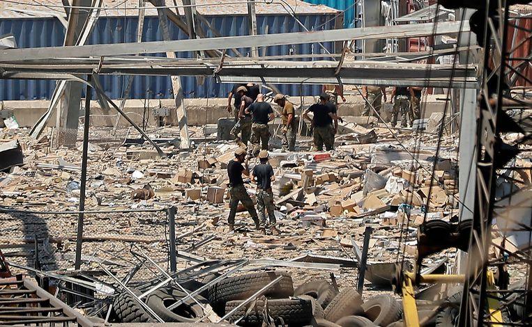 In de haven van Beiroet zoeken reddingswerkers en burgers naar overlevenden van de enorme explosie die gisteren een deel van de stad verwoestte.  Beeld AFP
