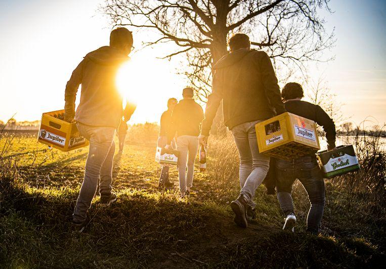 Jongeren lopen weg met hun drank na een illegaal feestje aan de Maas, 22 februari. Beeld Koen Verheijden