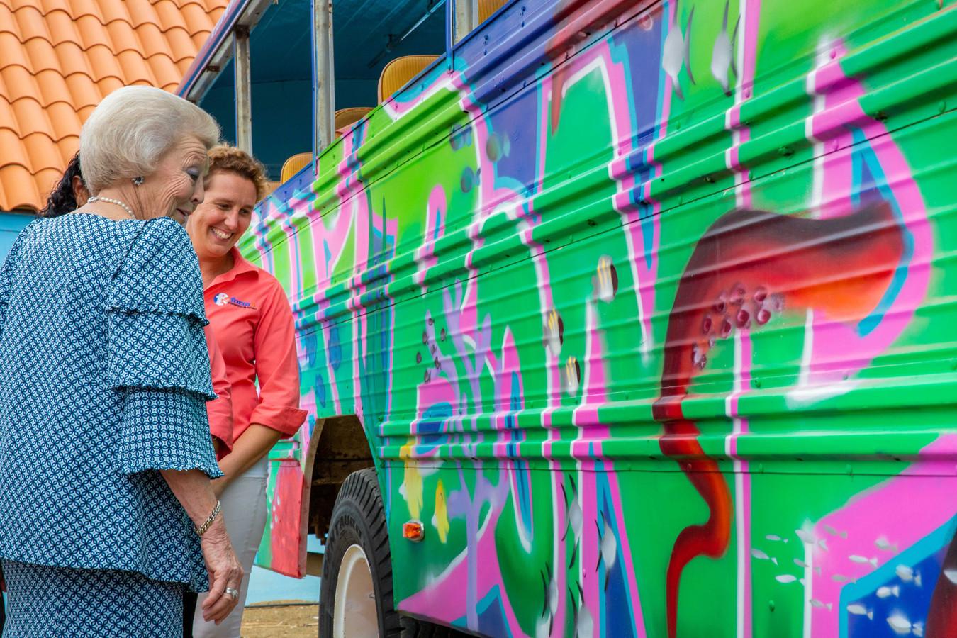 Prinses Beatrix bekijkt een 'muur'-schildering van jongeren op een toeristenbus.