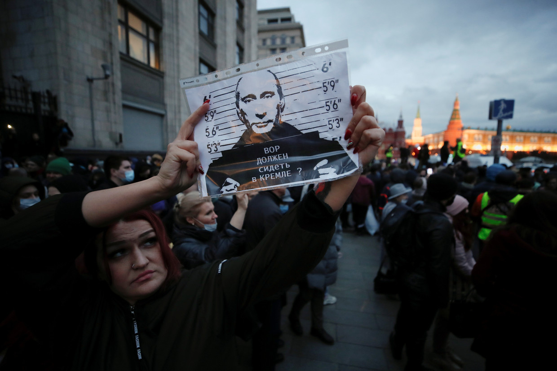 Navalny-aanhangers demonstreren afgelopen woensdag in de straten van Moskou. 'Hoort een dief thuis in het Kremlin?', staat er op het pamflet van deze demonstrante te lezen. Beeld REUTERS