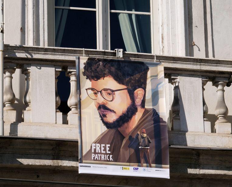 Een banier waarop de vrijlating van Patrick Zaki wordt gevraagd aan een balkon van het gemeentehuis in Turijn.  Beeld EPA