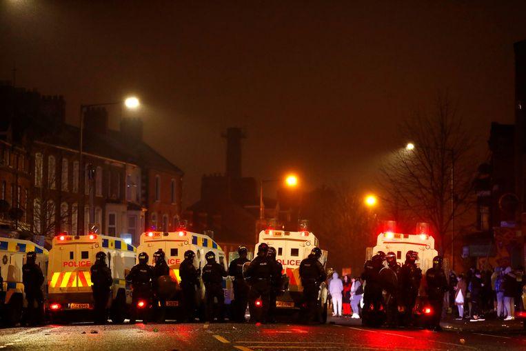 Politiemensen staan bij hun voertuigen in Belfast. Beeld REUTERS
