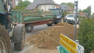 Tractor met kar vol grond kantelt in Heusden