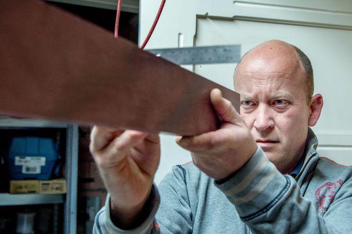 Marcel Rasing checkt de hoek van een stuk hout.