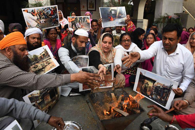 Mensen brengen een eerbetoon aan slachtoffers van de rellen.  Beeld AFP