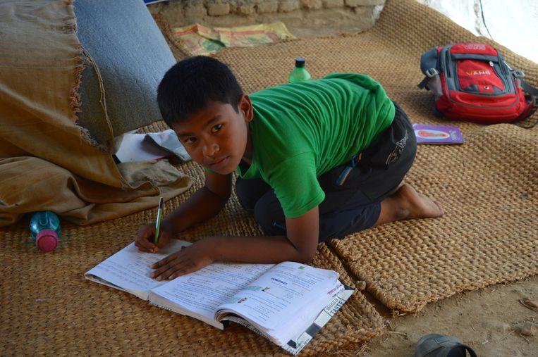 Safal Shrestha maakt zijn huiswerk in een tent. Beeld Lucia de Vries