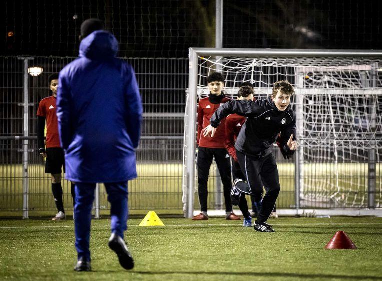 Voetballers van Zeeburgia tijdens een avondtraining. Na invoering van een avondklok is het niet meer toegestaan om na 21.00 uur zonder geldige reden buiten te zijn. Buiten sporten mag dan ook niet meer. Beeld ANP