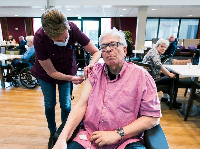Bewoner Dick Steinmetz van woon- en zorgcentrum De Wulverhorst wordt als eerste ingeënt tegen corona.