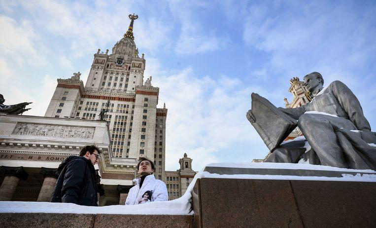 Studenten in gesprek voor het hoofdgebouw  van de Staatsuniversiteit in Moskou. De universiteit is gisteren weer begonnen met fysieke lessen, maar studenten moeten nog wel mondkapjes dragen.  Beeld AFP