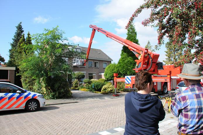 Een man wordt met een hoogwerker uit zijn huis gehaald.