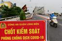 In Hanoi, de hoofdstad van Vietnam, controleert deze politieman het verkeer bij een coronacheckpoint. Een groot deel van het land is in lockdown door de snelle verspreiding van de deltavariant.