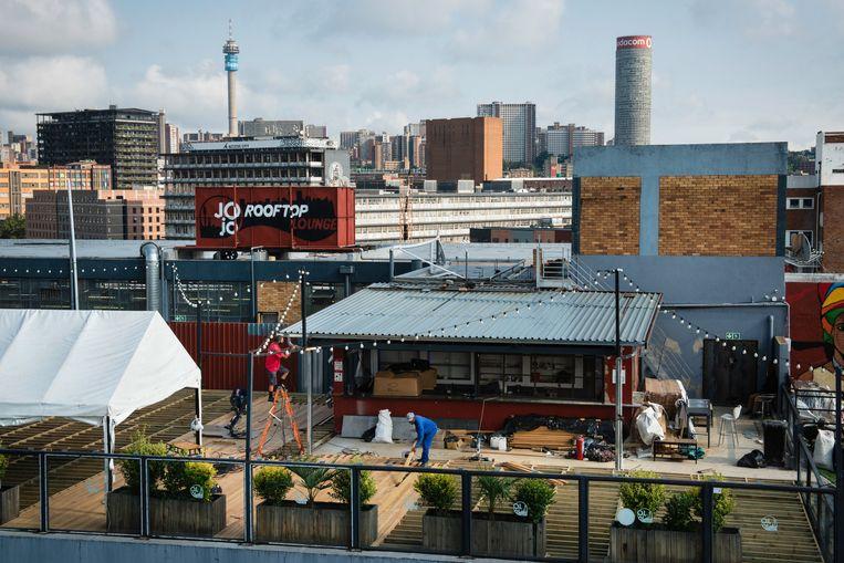 Werklui knappen de entree op van een bar op een dak in de wijk Maboneng. Op de achtergrond het zakencentrum van Johannesburg. Beeld Bram Lammers