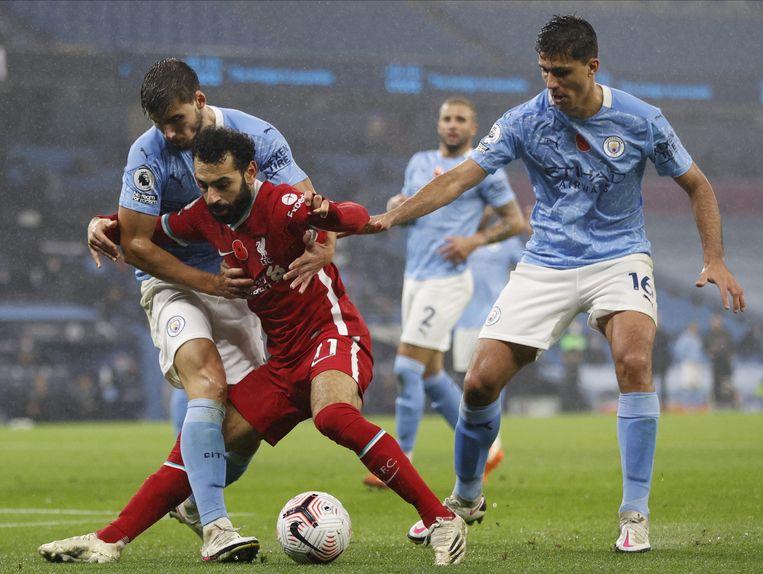 Mohamed Salah (midden) in actie tegen Rodrigo (rechts) en Ruben Dias (links) van Manchester CIty.  Beeld EPA