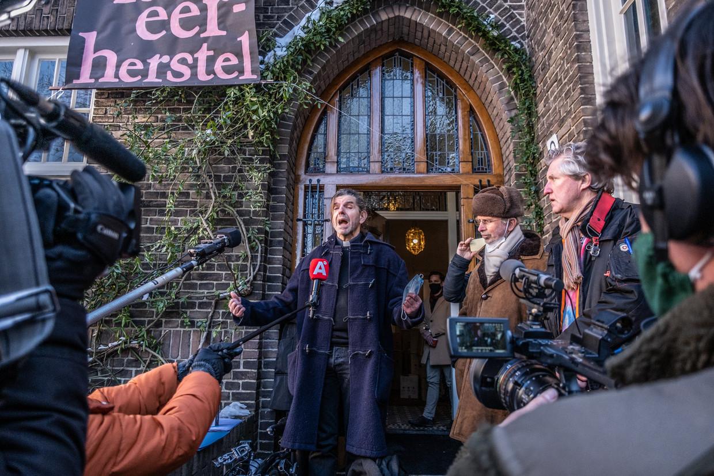 Pastoor Pierre Valkering van de Vredeskerk in Amsterdam doet vrijdagochtend zijn verhaal tijdens zijn uitzetting.  Beeld Joris van Gennip