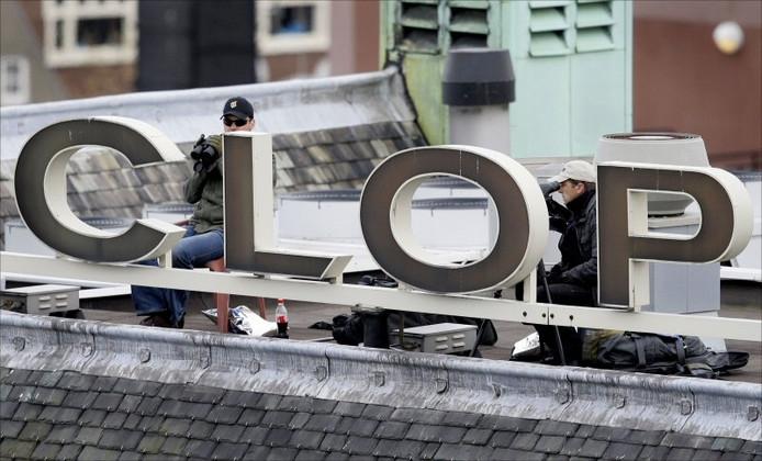 Vanaf het dak van modewinkel Peek & Cloppenburg hielden politieagenten gisteravond de Dam in de gaten, waar koningin Beatrix de nationale dodenherdenking bijwoonde. foto ANP