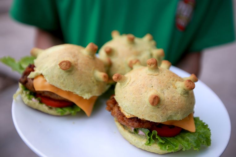 epaselect epa08324019 A man holds up coronavirus-themed burgers at a pizza restaurant in Hanoi, Vietnam 26 March 2020. The burger is currently sold for 65,000 VND each (around 2,5 Euros)  EPA/LUONG THAI LINH  ATTENTION: This Image is part of a PHOTO SET