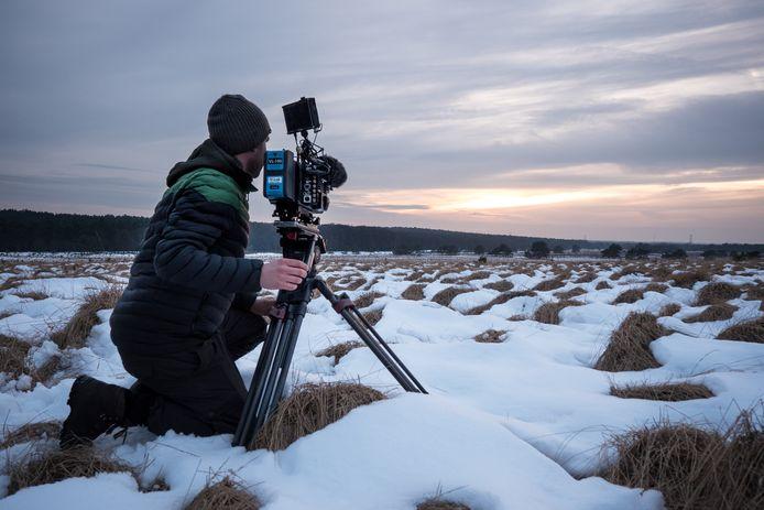 ,,Als ik ergens een hekel aan heb, is het aan kou'', aldus Dick. Hier in de sneeuw om een zonsondergang te filmen.