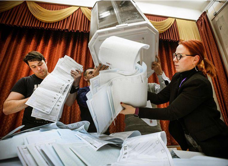 De stembussen worden leeggemaakt in een stemkantoor in Moskou: het tellen kan beginnen. Beeld AFP
