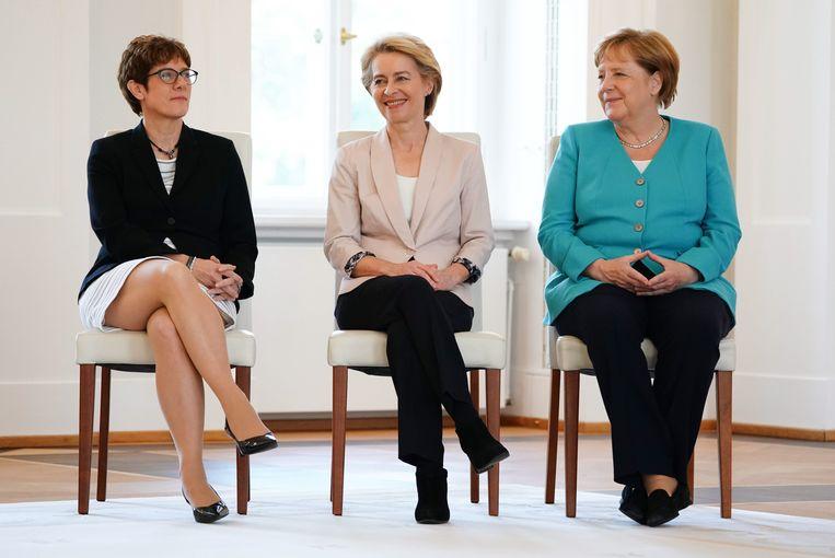Aankomend voorzitter van de Europese Commissie Ursula von der Leyen (midden) tijdens de overdracht van haar Duitse ministerschap van defensie aan Annegret Kramp-Karrenbauer (links), afgelopen woensdag in Berlijn. Rechts bondskanselier Angela Merkel.  Beeld EPA