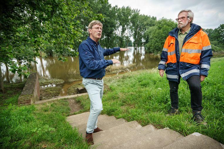 Bestuurder Jos Teeuwen (hoogwater bescherming en kering, links) en Mart Peters (vrijwillige dijkwacht, oranje jas) vertellen langs de Maas wat er sinds 1995 allemaal verbeterd is.   Beeld Maikel Samuels