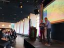 Ruud Overes van de stichting Parkinson2Beat wordt in het Parktheater in Eindhoven ondervraagd door dagvoorzitter Roland Kleve van de Bredase hbo-opleiding BUAS. Op de achtergrond wethouder Marcel Oosterveer.
