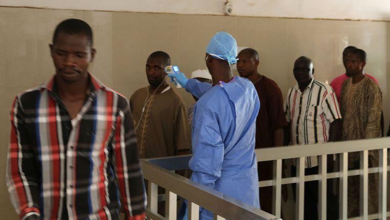 Een gezondheidsmedewerker checkt de temperatuur van inwoners van Guinee om te kijken of ze besmet zouden kunnen zijn met het ebola-virus. Beeld AP