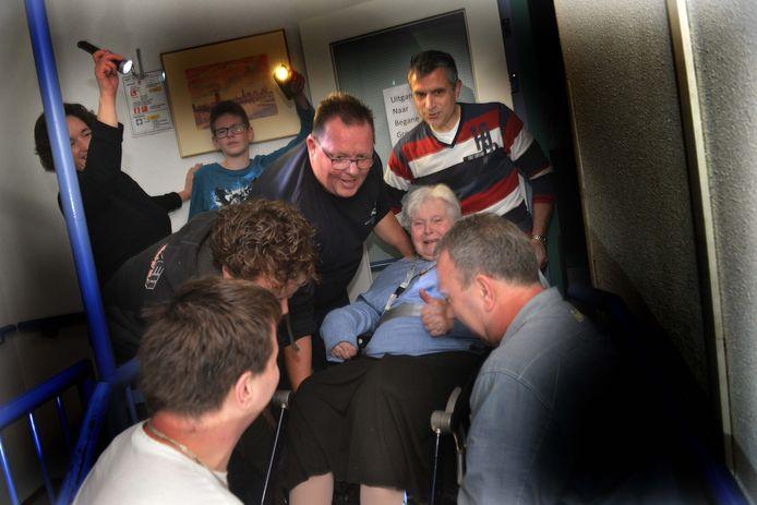 Vrijwilligers van de brandweer dragen bewoners met rolstoel naar boven in het Elisabethhof in Culemborg.