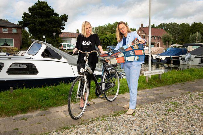 Wethouder Corine Bronsveld (gemeente Maassluis) en wethouder Wendy Renzen (gemeente Midden-Delfland) bekijken de nieuwe routekaart Delflandse Trekvaarten, met 19 wandel-, fiets- en vaarroutes.