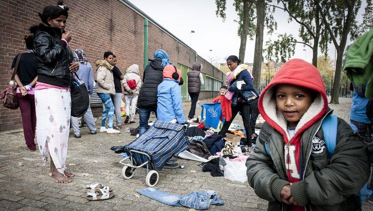 Vluchtelingen zoeken kleding uit die buurtbewoners hebben gebracht naar een sportcentrum in Rotterdam. Beeld anp